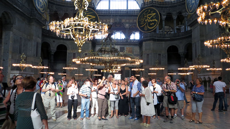 A group of tourists gathered near the apse of Haigia Sophia