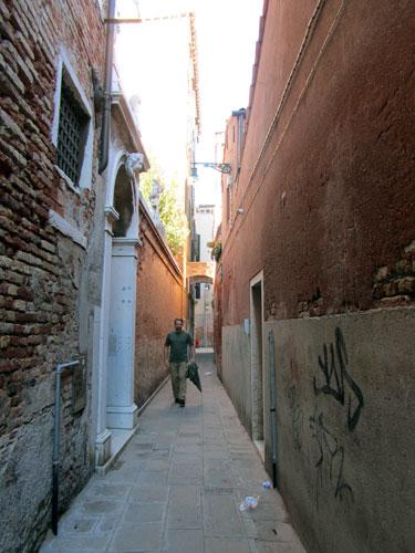 J.D., walking down a narrow street